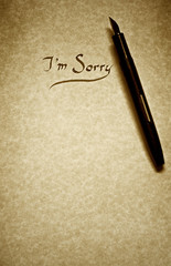 i am sorry leter being written in calligraphy on parchment