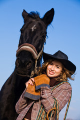 Lovely blond woman in a hat standing by horse in a field