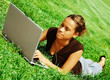 Beautiful young woman typing on a laptop in a green field.