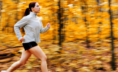 Beautiful young woman running in a fall forest.