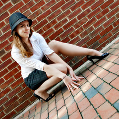 Fashionable young woman posing in front of a brick wall.