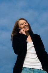 the girl speaking on the mobile phone in front of cloudy sky