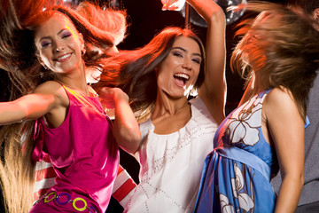 Photo of joyful teenage girls having fun on dance floor