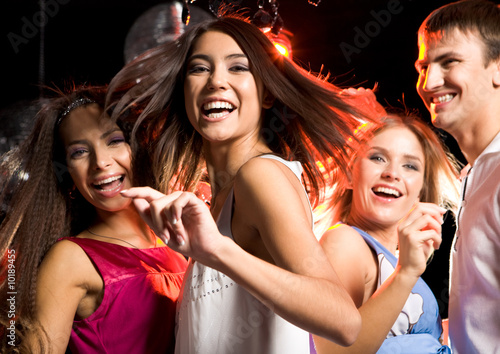 Portrait of laughing girl dancing among her friends