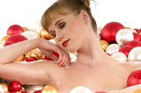 Young sexy model sleeping in bathtub full of Christmas balls poster