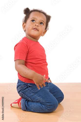 Adorable african baby kneel down over wooden floor