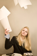 young tired business woman throwing papers into the air