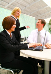 businesswoman typing on laptop and two coworkers