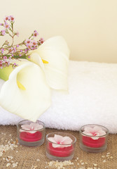 Relaxing spa scene with a white rolled up towel, white lillies