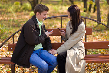 Young couple dial phone numbers a mobile phones