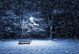View of bench and shining lantern through snowing. Night shot..
