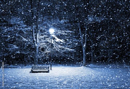 View of bench and shining lantern through snowing. Night shot..