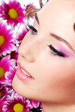 Fototapety Face of a young beautiful woman. Flowers on the background