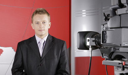 Presenter in TV studio in front of the camera and viewers