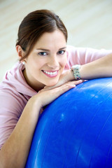gym woman doing pilates exercises on a blue ball
