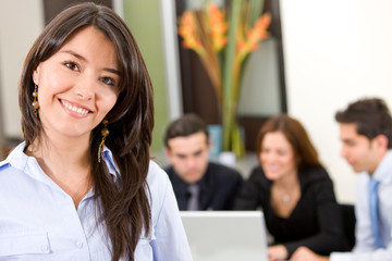 busines woman in an office smiling with her team
