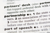 A close up of the word partnership from a dictionary poster