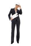 Businesswoman wearing hardhat holding blueprint poster