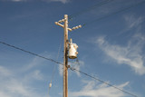Transformer on wooden pole with wiring and insolators poster