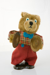 Wind-up teddy bear with brass cymbals, isolated against white