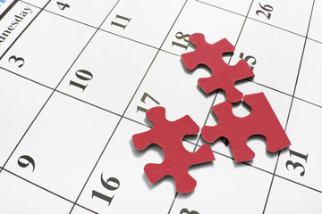 Red Jigsaw Puzzle Pieces on Calendar