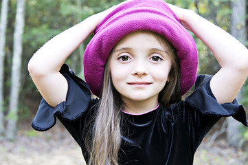 Little girl wearing a hat with hands on her head