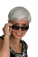 Mature woman peeking over the rim of her sunglasses