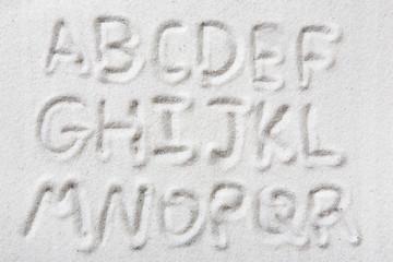 First half of an upper case alphabet written in sand