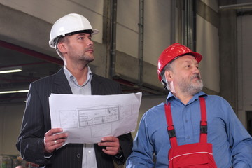 men in hardhats with blueprints