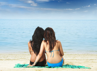 two girls sitting on the beach