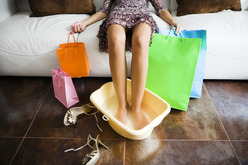 Woman soaking feet in water after long day shopping.