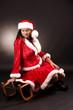 Frau im Weihnachtsmannkostüm mit Schlitten