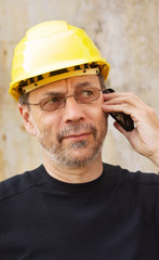 Mature man in yellow hard hat speaking on mobile phone
