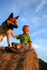 Little boy playing with the dog (Alsatian)