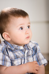 Portrait of cute baby boy ( 1 year old ) at home, looking away.