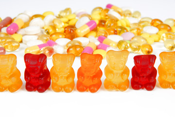 A stack of different coloorful tablets and gummy bears