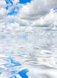 White fluffy clouds over large body of water poster