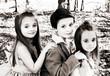 3 children posing for a portrait outdoors.