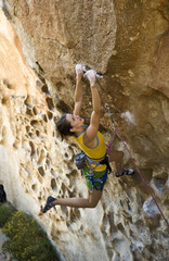 Female climber ascending an overhanging rock face,