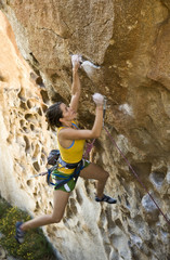 Female climber ascending an overhanging rock face.