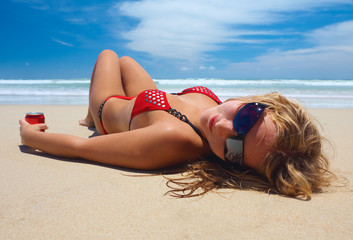Attractive girl is lying on the beach with can of cola