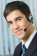 Portrait of happy support operator in headset at workplace