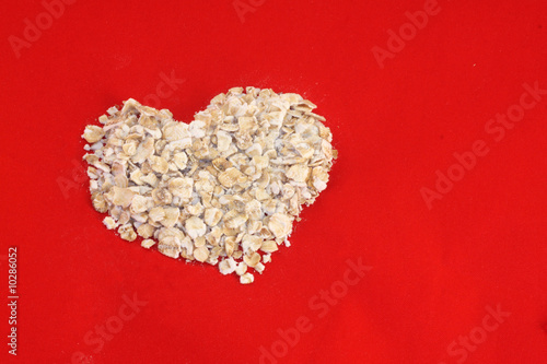 Dry rolled oats in a heart shape on a red background