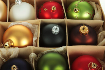A group of christmas balls in a paper box, multiple colors