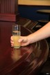 Hand holding a drink on a wooden pub or bar counter