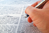 a hand holds a fountain-pen above a newspaper closeup