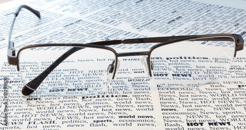 we take all news, glasses above a newspaper closeup