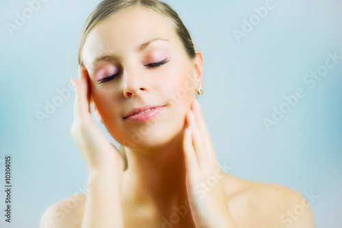 Young beautiful woman massaging her face.