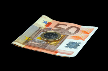 An isolated to black image of a 50 euro note and a 1 euro coin