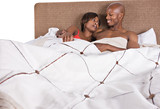 african american couple in bed having fun